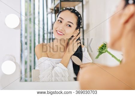 Smiling Charming Young Vietnamese Woman Sitting At Her Vanity And Brushing Hair