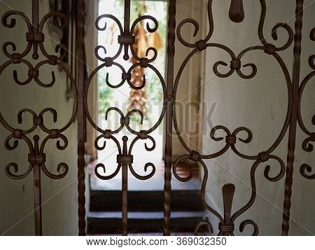 Details Of A Beautifully Crafted Curved Wrought Iron Door Gate With Blurred Yard In The Background