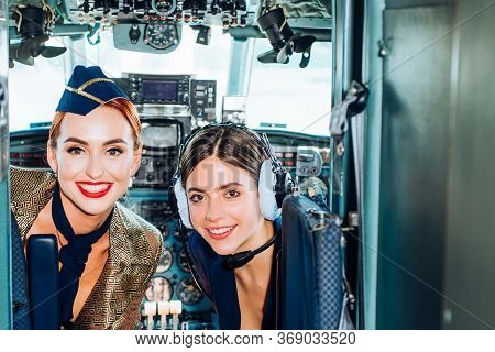 Woman Pilot In Aviation Headsets. Pretty Stewardess. Portrait Of Attractive Young Woman Pilot In Coc