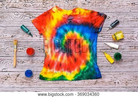 Brush And Paint For Fabric And T-shirt In Tie Dye Style On A Wooden Background. White Clothes Painte
