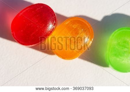 Colorful Lollipops On A White Background. Macro Photography Of Beautiful Candies In The Sunlight. Be