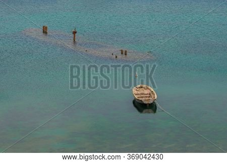 Old Wooden Boat And A Sunken Ship.