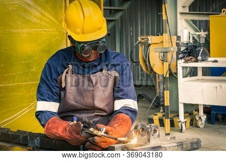 African woman gas welding  two brackets with a acetylene welding torch