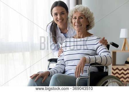 Caring Nurse Hug Elderly Disabled Woman In Wheelchair Posing Indoors