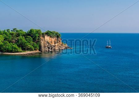 A Tourist Ship Sails Along A Rocky Coast On The Mediterranean Sea In Turkey. The Most Popular Touris