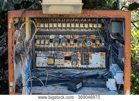 Rusty Electric Box With Fuses And Wires In The Dump Outside.