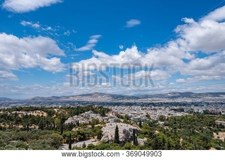 Athens City Against Blue Cloudy Sky In A Spring Day. Aerial View From Acropolis Hill. Attica, Greece