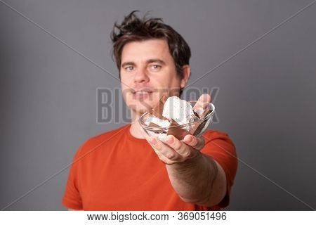 Young Man Holds A Plate Of Chocolate Ice Cream. Fanny Man With An Appetite Eats Ice Cream.