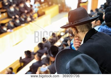 Orthodox Hasidim Listen To Their Rabbi During Mass Prayer In In A Synagogue.
