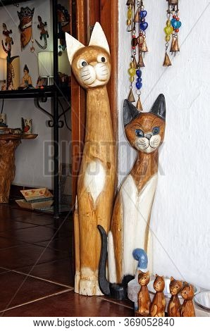 Tall Wooden Carved Cats Displayed In A Shop Doorway In The Village Centre, Mijas, Costa Del Sol, Mal