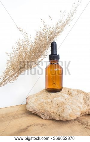 Bottle With A Pipette, Filled With Oil Or Essence Stands On A Stone On A Light Background.  The Aest