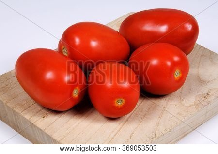 Red Ripe Plum Tomatoes On A Wooden Chopping Board.