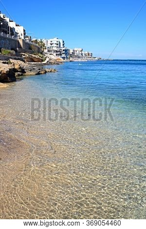 View Along The Beach And Shoreline With Buildings To The Rear, San Pawl, Malta, Europe.