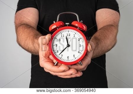Caucasian Man In Black Tshirt Holding Vintage Red Alarm Clock In His Hands