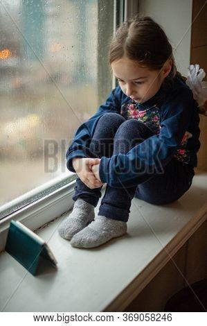 Beautiful Cute Caucasian Female Kid Sitting On Windowsill. A Little Girl Sits On A Windowsill And Lo