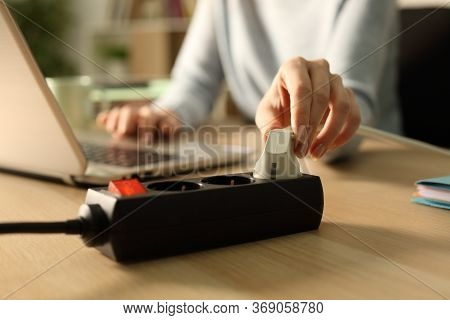 Close Up Of Woman Hand Plugging Plug On A Power Strip Socket At Night Using Laptop On A Desk At Home