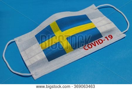 Medical Face Mask With  Flag Of Sweden And Covid-19 Text On Blue Background. Concept Of Coronavirus
