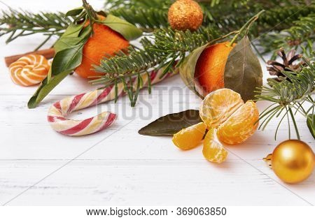 Slices Of Fresh Peeled Tangerine, Whole Tangerines, Spruce Branches, Lollipops, Golden Christmas Bal