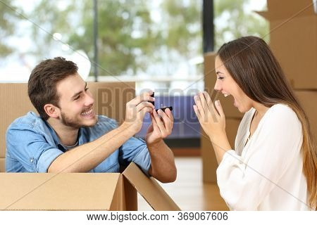 Happy Man Proposing To Excited Girlfriend With Wedding Ring While Moving At New Home Surrounded By B
