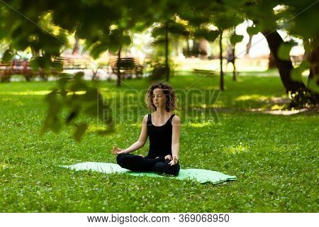 Attractive And Tranquil Woman Sits In Lotus Position Under Tree. Yoga And Meditation, Concentration