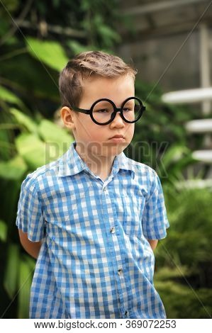 Boy In A Checkered Shirt And Glasses Stands Discontented