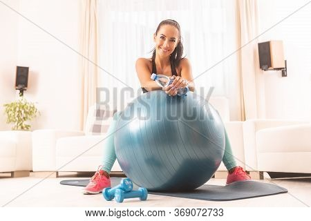 Smiling Brunette Sits Behind A Fit Ball After An Exercise At Home, Holding A Bottle Of Water.