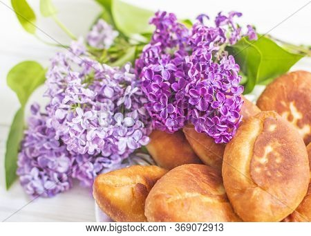 Piroshki - Russian Baked Puff Pastry With Cabbage Fillings And Bouquet Of Lilacs. Traditional Russia
