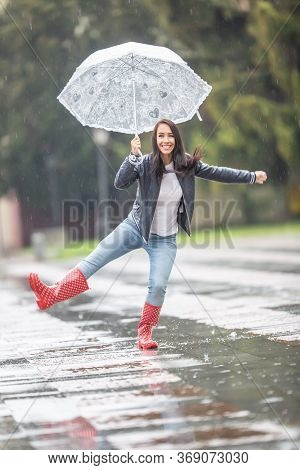 Young Woman Dances In The Rain In The Park, Holding An Umbrella, Wearing Rainboots.