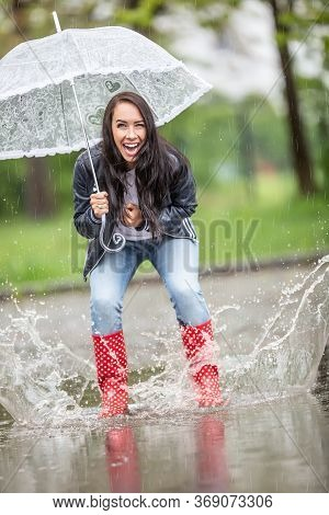 Happy Girl Jumping In Puddles In Rainboots, Laughing, Holding An Umbrella Above Her.