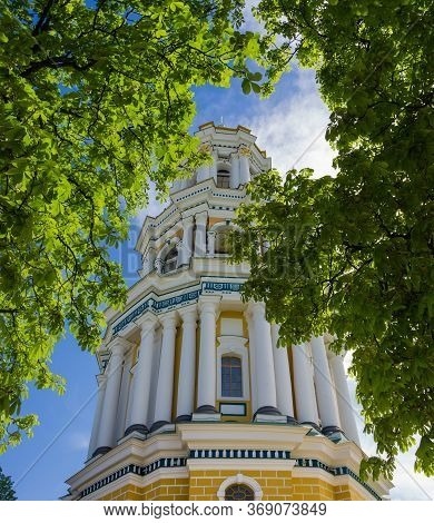 Great Belltower Of The Kyiv Pechersk Lavra, Ukraine. Bottom Up View Through The Branches Of Chestnut