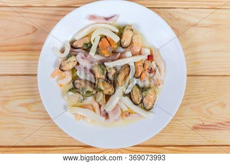 Various Seafoods - Shrimp Tails, Mussels Peeled From Shells, Calamari Slices In The Oil Sauce On The