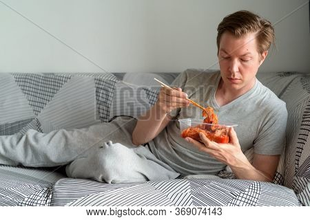 Young Handsome Man Eating Kimchi While Lying Down On The Sofa At Home