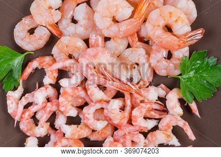 Cooked Peeled Tails Of King Prawns And Usual Shrimps On The Brown Dish, Fragment Top View, Backgroun