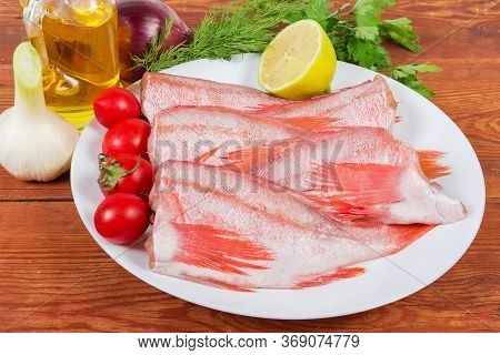 Raw Headless Gutted Carcasses Of Redfish Also Known As Ocean Perch On The Dish With Lemon And Cherry