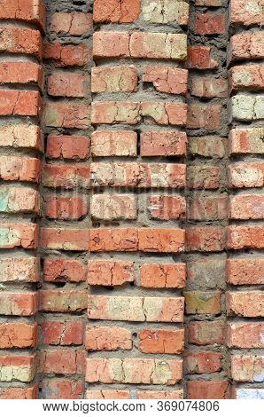 Red Brick Wall With Ledges And Cavities Background. Old Cracked Clay Brick Wall. Basis For Solving V