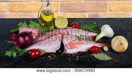 Raw Headless Gutted Carcasses Of Redfish Also Known As Ocean Perch Among The Spices, Fresh Vegetable