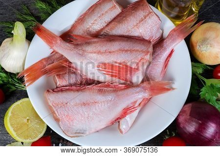 Raw Headless Gutted Carcasses Of Redfish Also Known As Ocean Perch On Dish Among The Spices On The B
