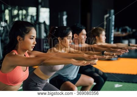 Close-up Of Group Of Athletic Young Asian People In Sportswear Doing Squat And Exercising At The Gym