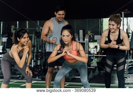 Group Of People Cheering On Their Asian Female Friend Doing Squats In Fitness Gym. Working Out Toget