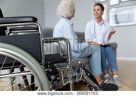Physiotherapist Elderly Woman Talking Seated On Sofa, Focus On Wheelchair