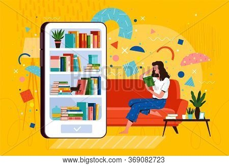 Young Woman Sits On A Sofa And Reads A Book From A Mobile Library On The Phone. E-book Reader And Di