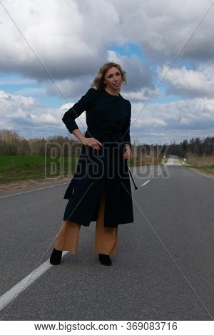 Attractive Blond Woman Walking Away On An Empty Countryside Road That Leads To The Horizon