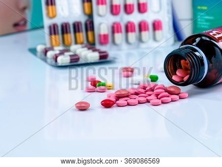 Tablets Pills Spread Out Of Amber Glass Drug Bottle On Blurred Capsules In Blister Pack. Red And Pin