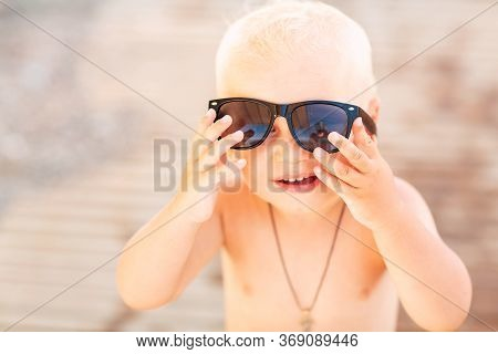 Cute Baby Boy Wearing Sunglasses On The Beach