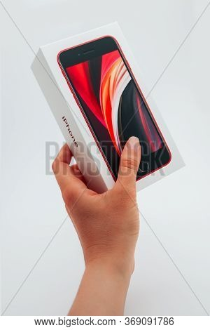 France, Paris - May 1, 2020: A Hand Holding A New Red Apple Iphone Se 2nd Generation Box On White Ba