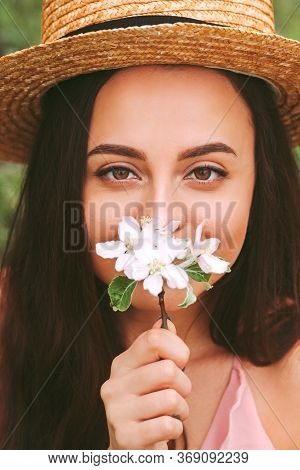 Closeup Young Carefree Hippie Woman In Straw Hat Posing With Blossom Flower In Hand And Smiling On S