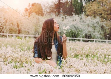 Calm Beautiful Hippie Girl In Denim Jacket Relaxing Sitting On Dandelion Field. Happy Young Carefree