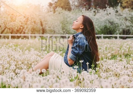 Portrait Young Carefree Hippie Girl In Denim Jacket Relaxing On Summer Blossom Countryside Garden. H