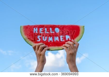 A Piece Of Watermelon Against A Blue Sky. Childrens Hands Are Holding A Slice Of Watermelon With The