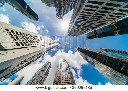 Skyscraper Tower Buildings In Business District, Singapore City. Cloud And Sun Flares On Sunny Day S